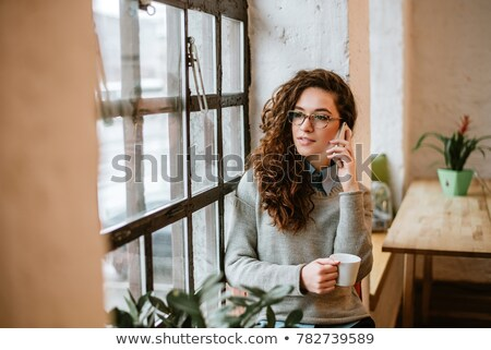 portrait of a pretty smiling girl talking on mobile phone stock photo © deandrobot