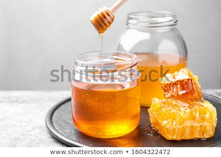 Sweet honey in a glass jar with wooden stick on a gray stone table. Jewish rosh hashanah holiday. Stock photo © artjazz