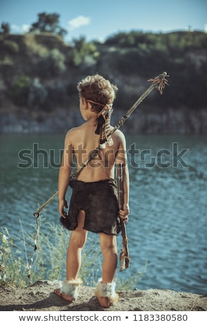caveman manly boy with stone axe and bow hunting outdoors stock photo © artfotodima