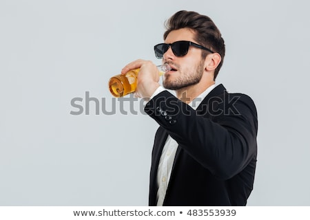Stylish handsome man in sunglasses shows the bottle stock photo © ruslanshramko