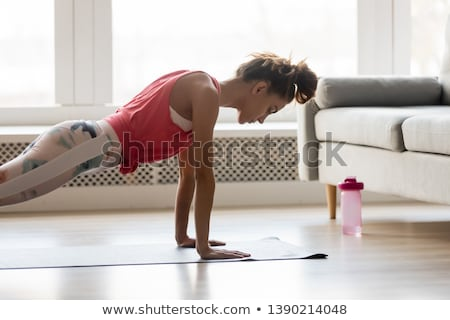 Sporty woman doing plank exercise in gym Stock photo © boggy