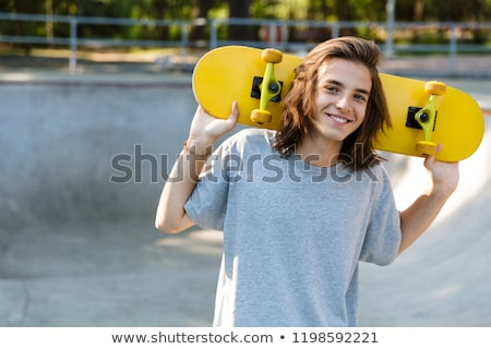Joyful young teenge boy spending time at the skate park Stock photo © deandrobot