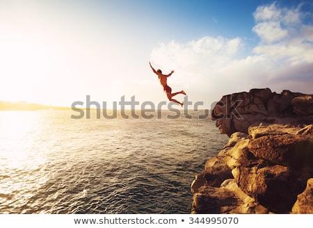 Man jumping off cliff into the water. Summer fun lifestyle Stock photo © galitskaya