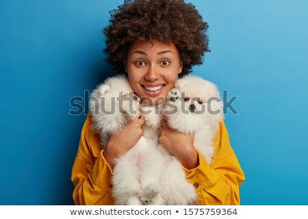 Animals, loyalty and people concept. Smiling brunette lady in oversized brown sweater plays with ped Stock photo © vkstudio