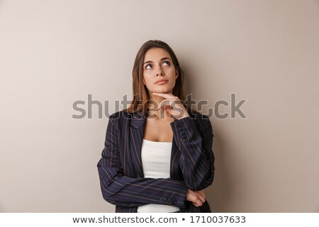 Image of young serious woman thinking and looking upward Stock photo © deandrobot