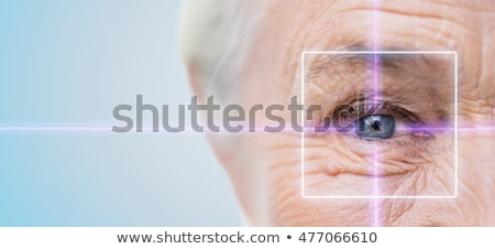 close up of senior woman eye with laser light Stock photo © dolgachov
