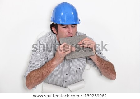 Fed-up tradesman biting a tile Stock photo © photography33