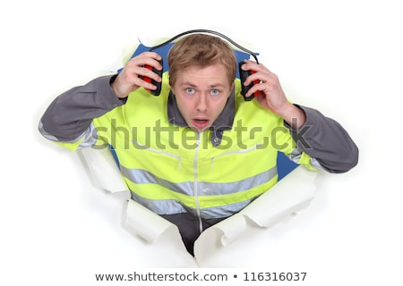 man with earmuffs emerging from poster Stock photo © photography33