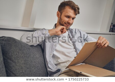 Front view Caucasian businessman writing on notepad looking at c stock photo © dgilder