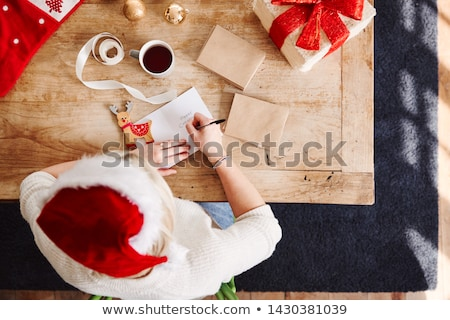 Woman wearing Santa Claus hat wrapping Christmas gift Stock photo © HASLOO