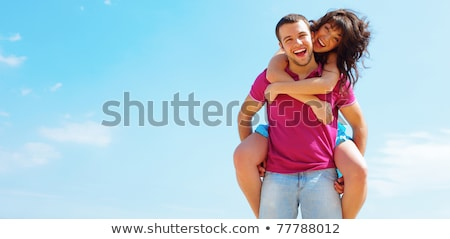 Happy young couple in casual cloths with a sky on background. Copyspace. Stock photo © deandrobot