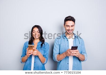 Vonzó fiatal nő küldés szöveges üzenet mobiltelefon bejárat Stock fotó © dash