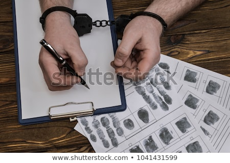 Police handcuffs and blank paper on investigator detective's wor Stock photo © stevanovicigor