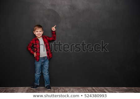 happy little boy standing over chalkboard stock photo © deandrobot