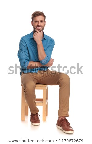 seated smiling young casual man holding chin stock photo © feedough