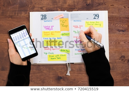 Empresário olhando lista programar diário Foto stock © AndreyPopov