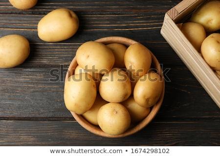 Raw potato in basket on wooden table closeup Stock photo © yelenayemchuk