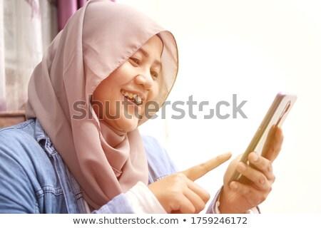 Muslim business woman holding a mobile phone. Stock photo © RAStudio