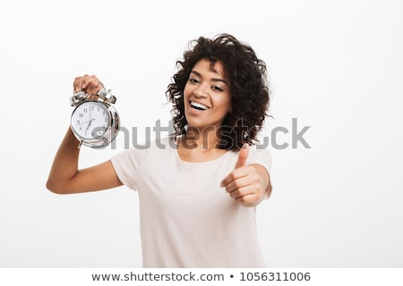 Pretty happy african woman standing and holding alarm clock Stock photo © deandrobot
