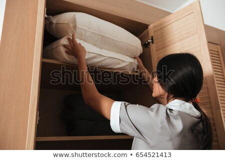 Hotel making putting bed pillows in a cupboard Stock photo © deandrobot
