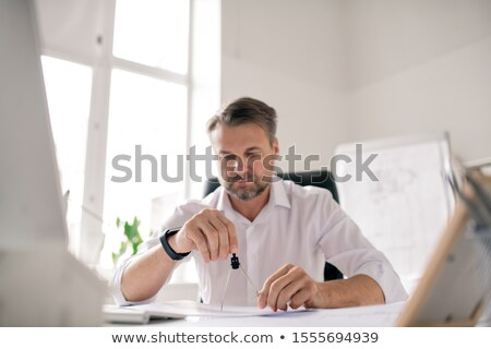 Mature bearded engineer in white shirt using dividers while working over sketch Stock photo © pressmaster