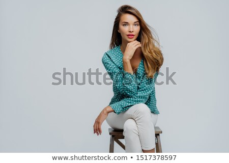Indoor shot of lovely businesswoman sits on chair, holds chin, wears polka dot blouse and white trou Stock photo © vkstudio