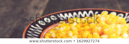 Banner of Canned corn in a brown bowl on wooden background. Stock photo © Illia