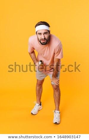 изображение недовольный молодым человеком прикасаться колено Сток-фото © deandrobot