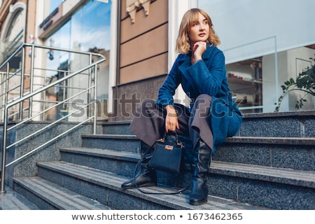 sitting young woman wearing extravagant boots Stock photo © phbcz