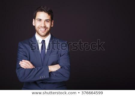 handsome man in a business suit on a dark background stock photo © konradbak
