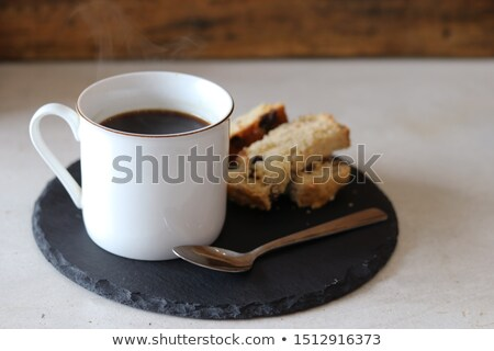 Bread bun and a cup of coffee with a spoon on white plates against a white background Stock photo © wavebreak_media