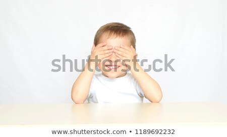 Portrait of little boy closing eyes with his hands at home Stock photo © HASLOO