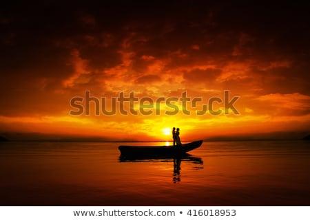Stockfoto: Silhouet · paar · zoenen · boot · rivier · zonsondergang