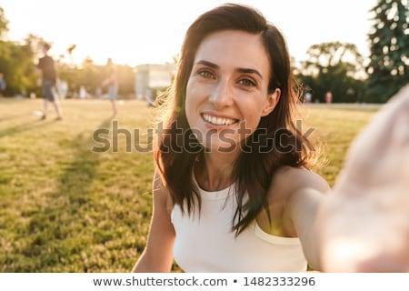 Brunette woman taking beautiful nature photo. Stock photo © lithian