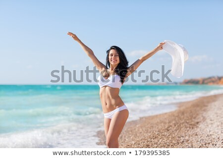 happy woman in swimsuit with raised hands on beach stock photo © dolgachov