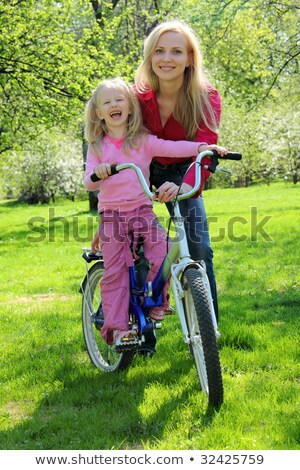 laughing girl on bicycle with mother in spring garden Stock photo © Paha_L