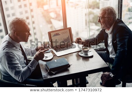 Two happy young businessmen sitting and talking on business meeting Stock photo © deandrobot