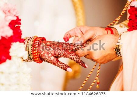 Groom putting ring on the brides finger Stock photo © jaykayl
