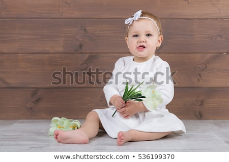 Stock photo: Ballerina in white dress sitting, studio background.