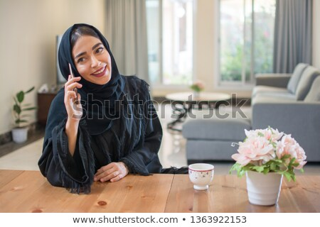 Stock photo: Young woman talking on a smartphone and drinking coffee while dr