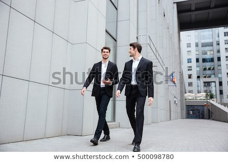 Happy young businessman walking outdoors. Stock photo © deandrobot