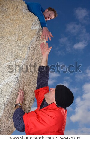 Climber offering hand to fellow climber Stock photo © IS2