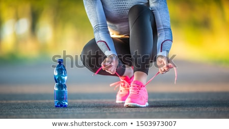young woman tying shoelaces before running stock photo © vlad_star