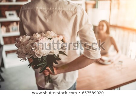 young woman holding flowers behind back stock photo © is2