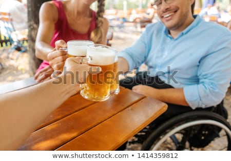 Friends in beergarden clinking glasses with beer Stock photo © Kzenon