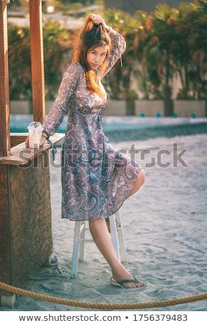 Young asian fashion woman drinking cocktail in a beach bar. Stock photo © artfotodima