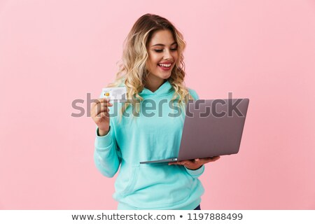 image of shopper woman 20s holding silver laptop and credit card stock photo © deandrobot