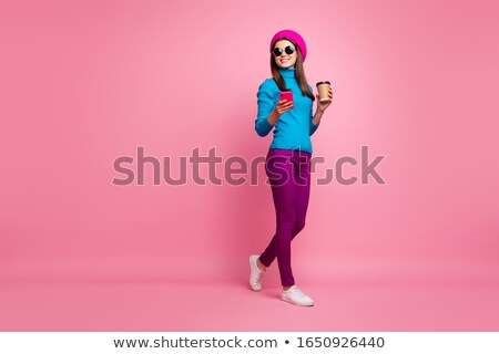 Beautiful woman isolated over blue background holding coffee chatting by phone. Stock photo © deandrobot