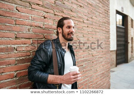 Photo of european unshaved man with tied hair standing over bric Stock photo © deandrobot