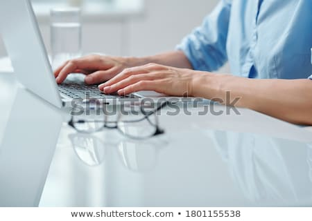 Human hands pushing keys of computer keyboard while sitting by desk Stock photo © pressmaster